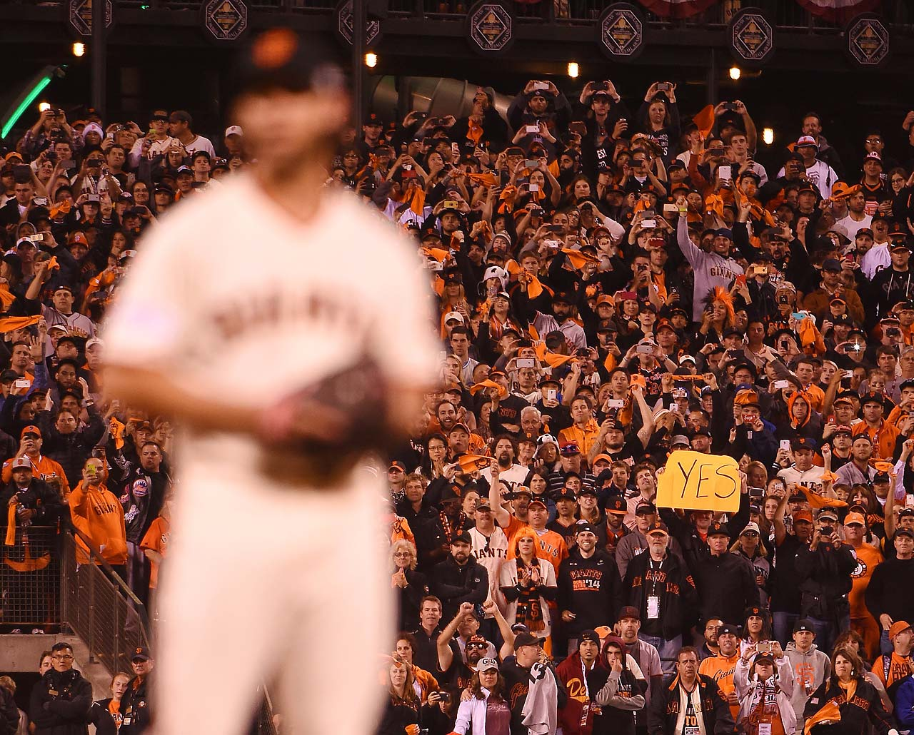 A Giants fan hold up his YES sign in the background as San Francisco moved within a win of capturing the World Series title as the series heads back to Kansas City.