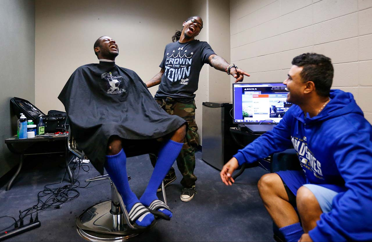Lorenzo Cain jokes around while getting a haircut before the start of the game.