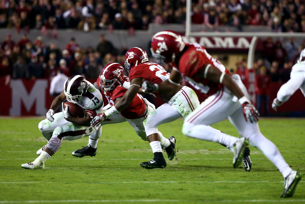 Running back Josh Robinson is stopped by Reggie Ragland (19), Landon Collins (26) and Geno Smith (24).