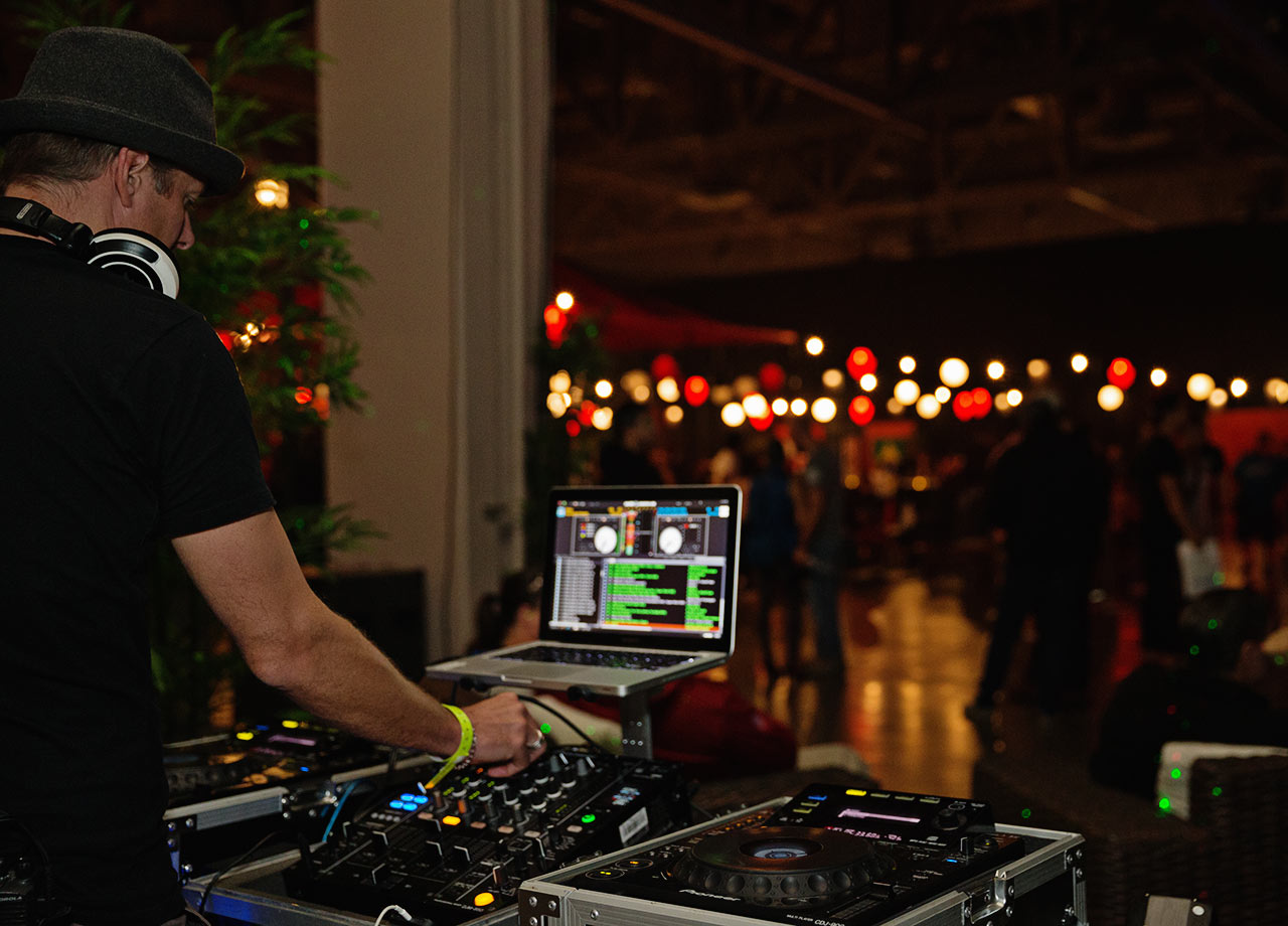 A DJ plays in the gathering area of the event.