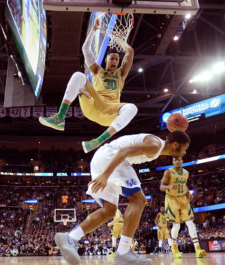 Notre Dame forward Zach Auguste searches for a spot to land after dunking against Andrew Harrison and Kentucky during the teams' Elite 8 duel at Cleveland's Quicken Loans Arena. Despite Auguste's 20 points, Kentucky prevailed 68-66 to advance to the Final Four.