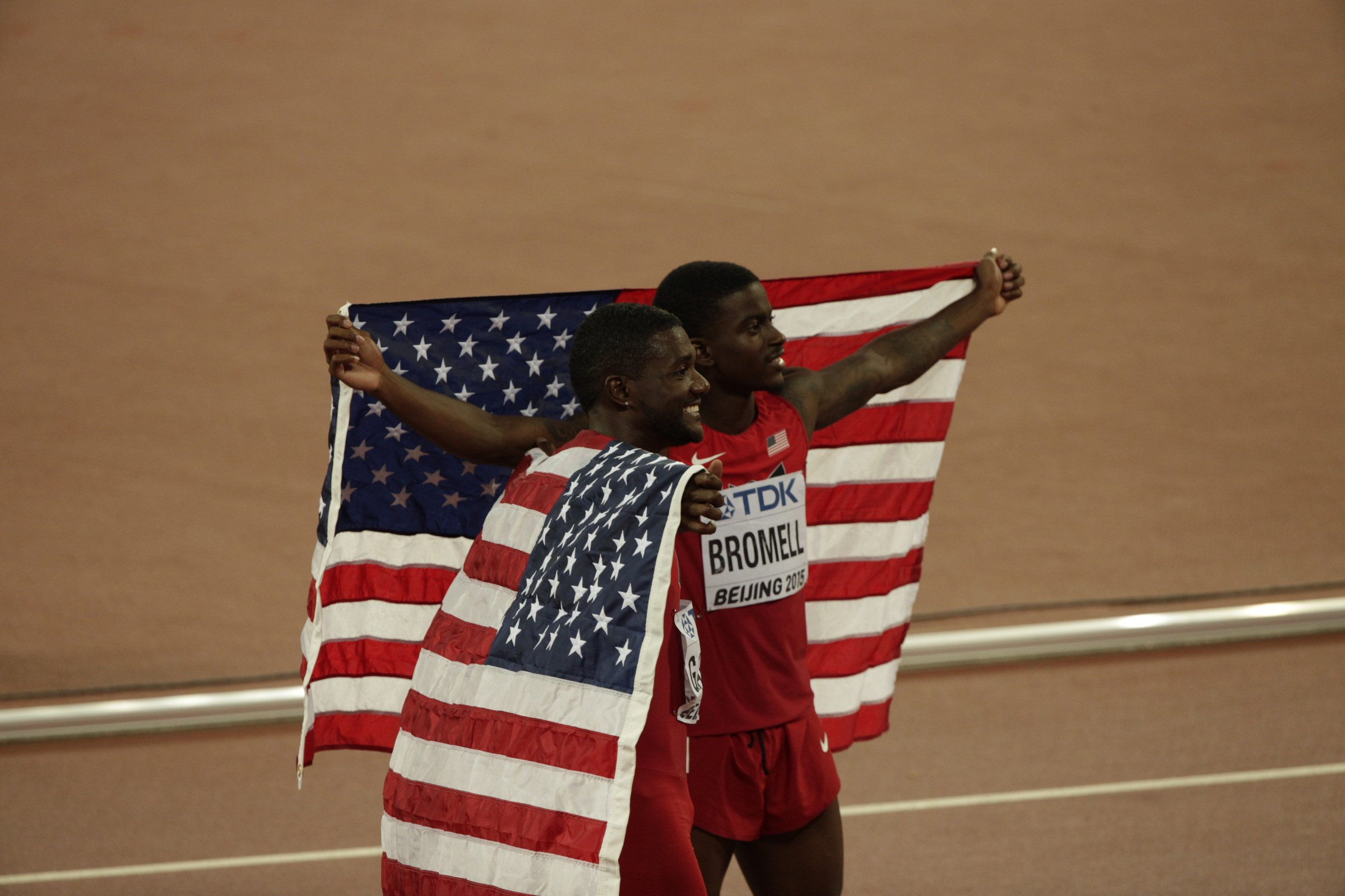 Silver medalist Justin Gatlin (USA) and bronze medalist Trayvon Bromell (USA) celebrate with U.S. flags after the men's 100-meter final.