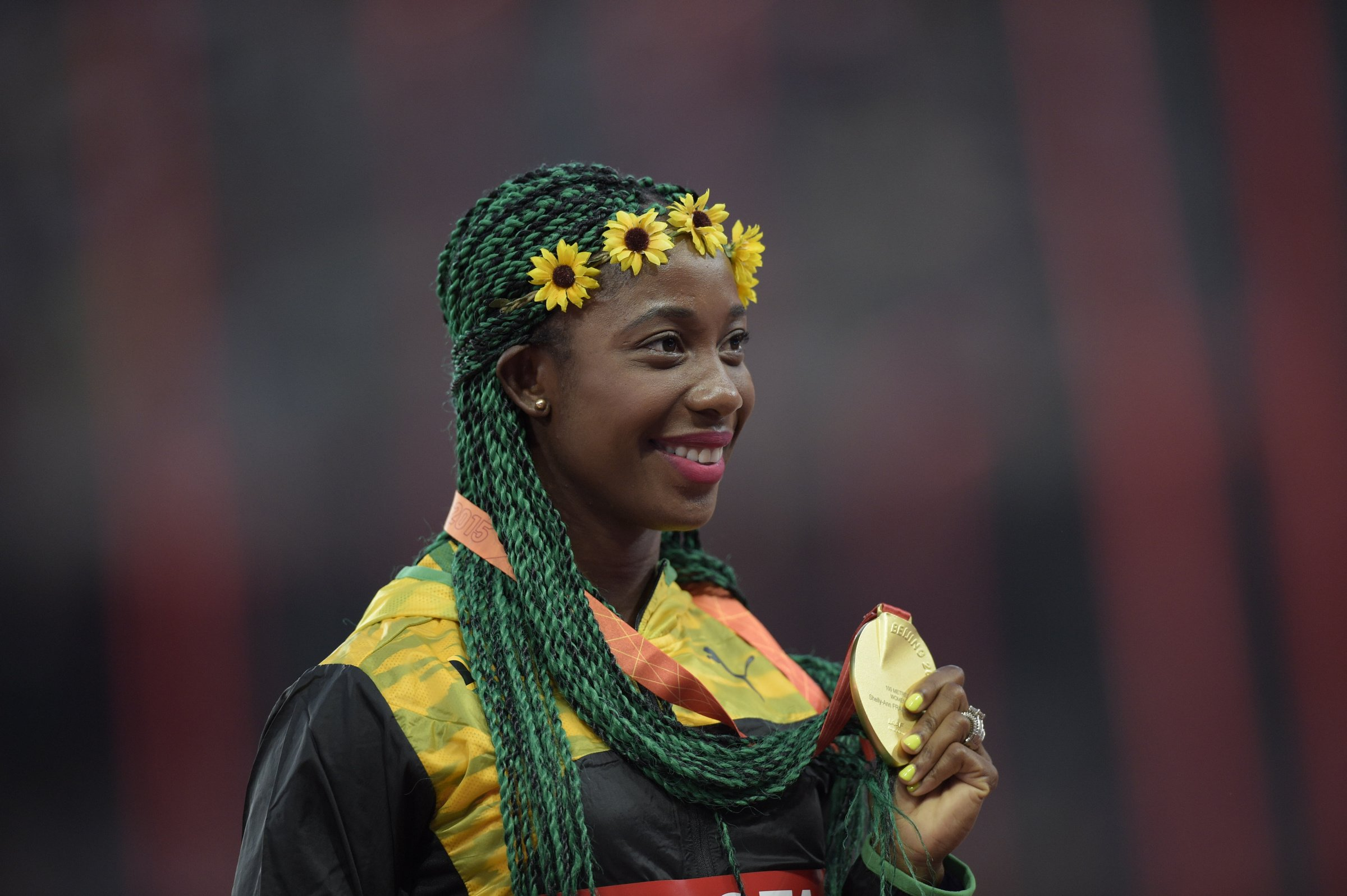 Shelly-Ann Fraser-Pryce (JAM) holds up her third 100-meter world championship gold medal.