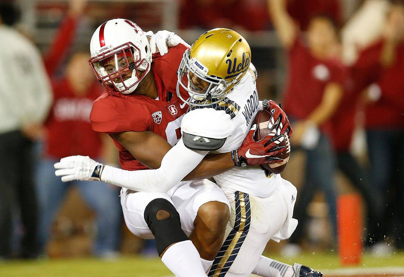 Francis Owusu of Stanford catches a touchdown pass up against the back of Jaleel Wadood of UCLA.