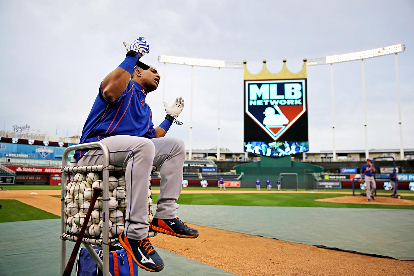 Yoenis Cespedes of the New York Mets sits on a basket of balls at a game against the Kansas City Royals.