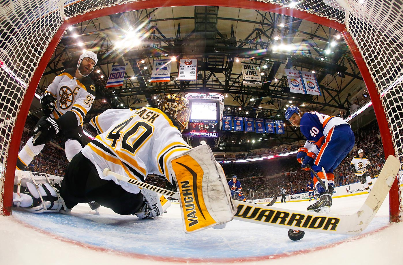 Boston Bruins goalie Tuukka Rask makes a stick save on a shot from Michael Grabner of the New York Islanders.