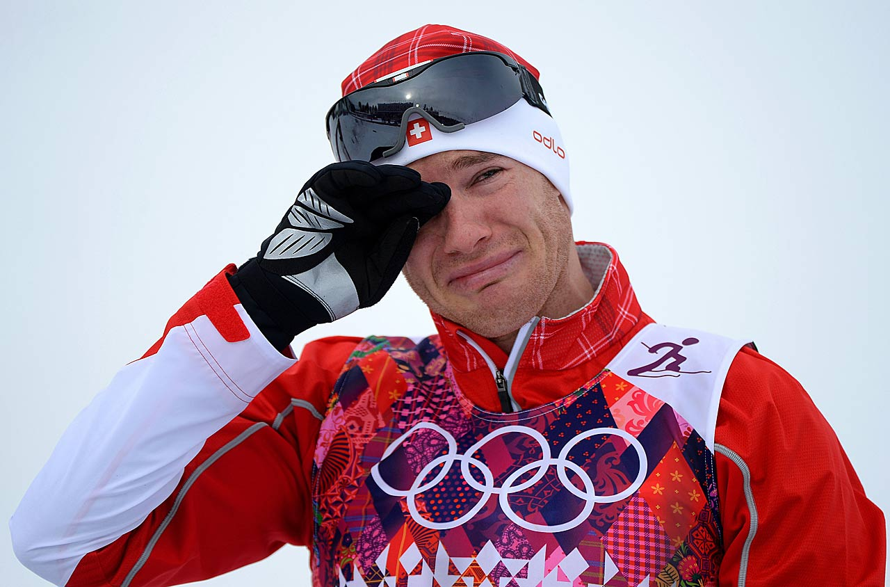 Gold medalist Dario Cologna of Switzerland reacts on the podium during the flower ceremony for the Skiathlon 15 km Classic + 15 km Free.