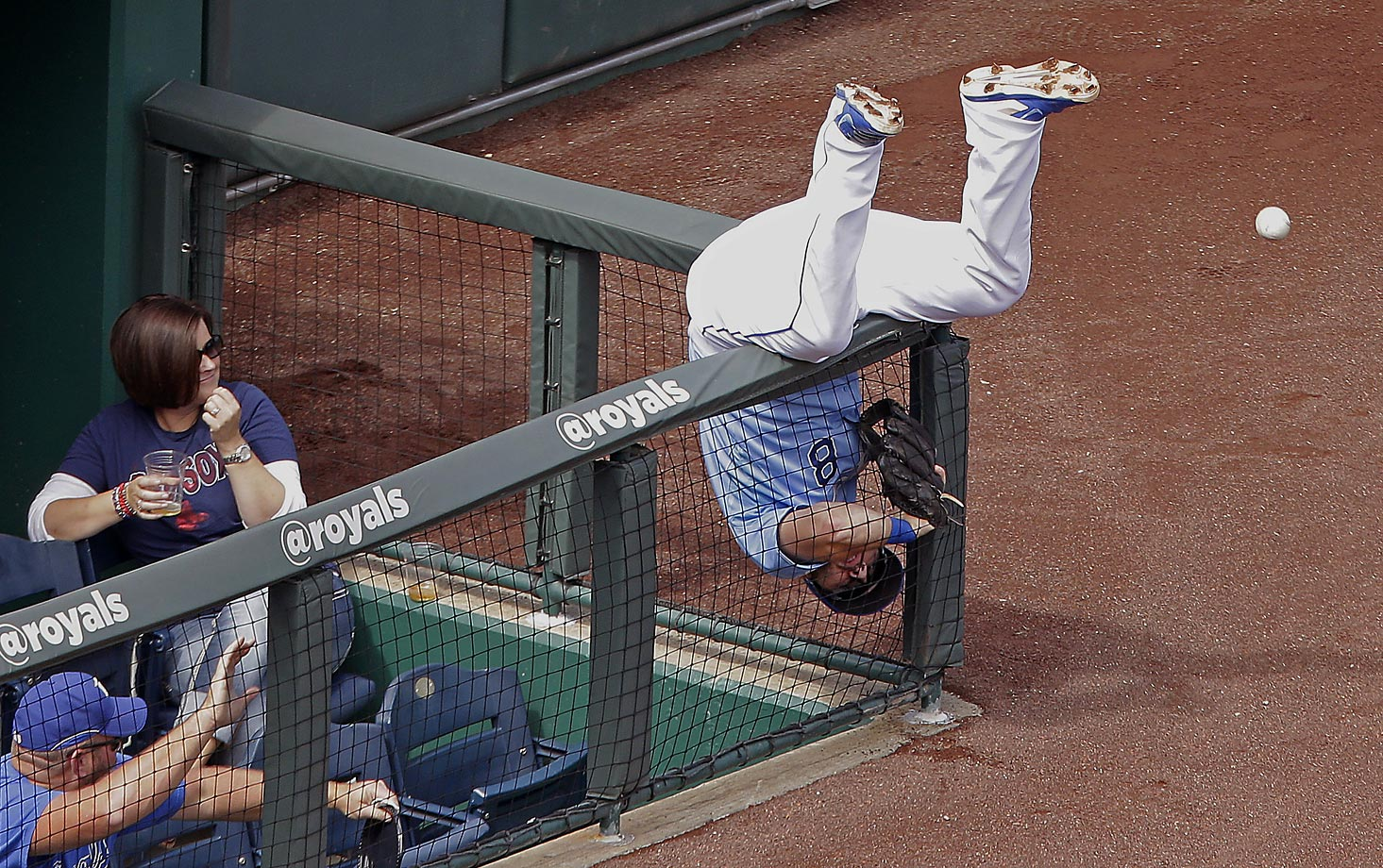Kansas City Royals third baseman Mike Moustakas gets hung up in the fencing while trying to catch a foul ball in a game against the Red Sox.