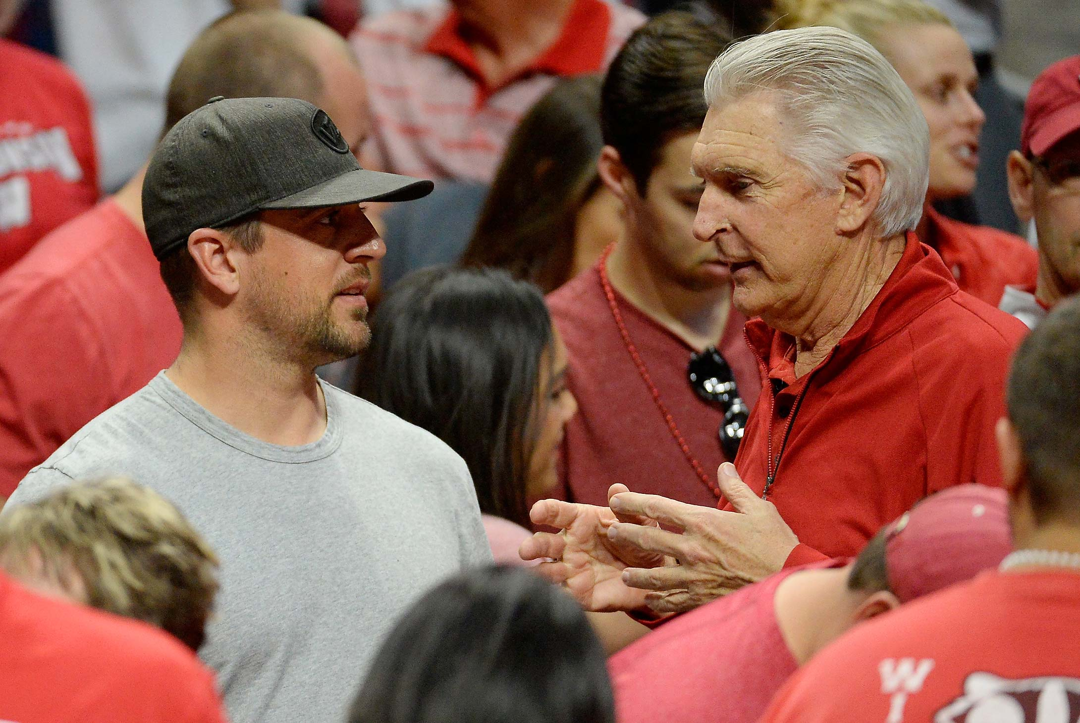 NFL quarterback Aaron Rodgers talks with golfer Andy North during the 2015 West Regional Semifinal between Wisconsin and North Carolina.