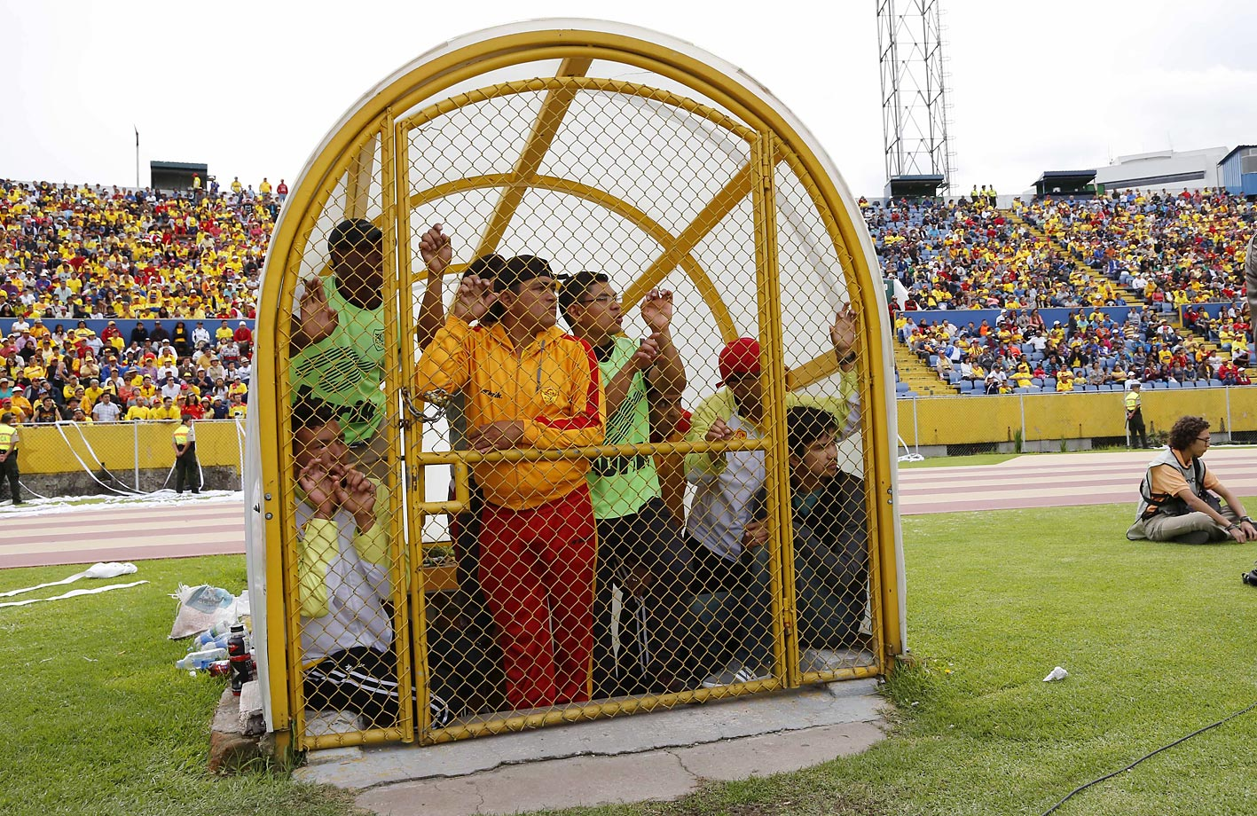 Stadium assistants watch a game between the Aucas and Liga de Portoviejo from inside a gated entry on the sideline in Quito, Ecuador.