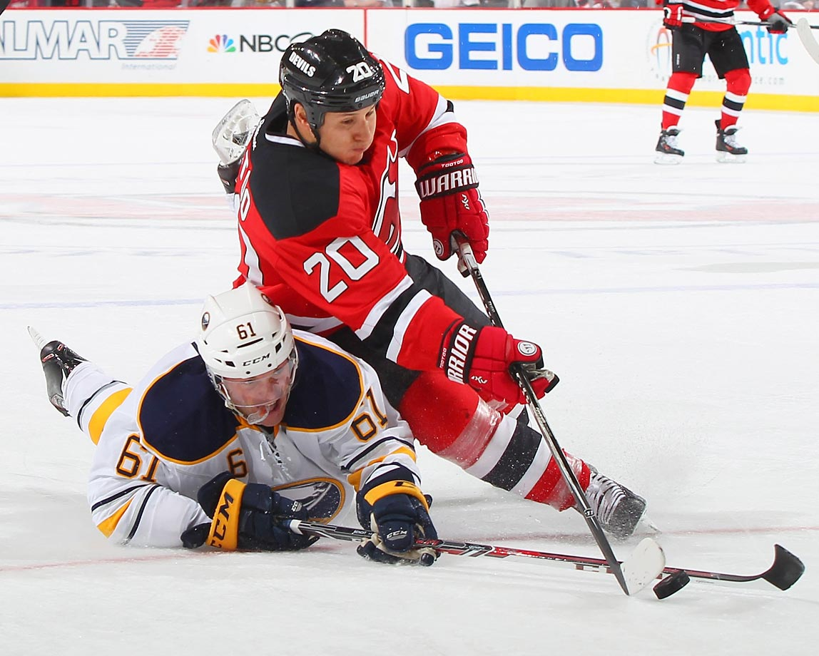 Andre Benoit (61) of the Buffalo Sabres and Jordin Tootoo of the New Jersey Devils battle for a loose puck.