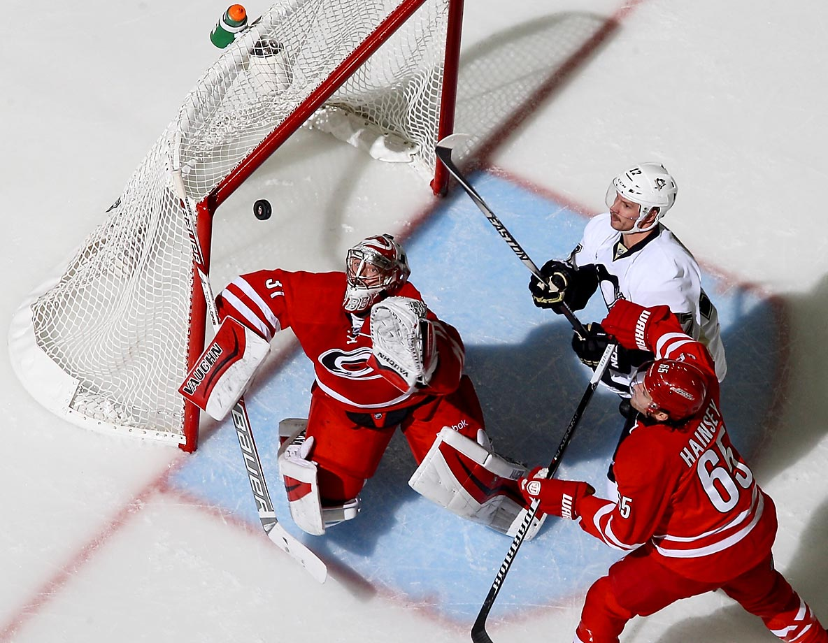 Anton Khudobin of the Carolina Hurricanes keeps his eye on the puck as Ron Hainsey and Blake Comeau of the Pittsburgh Penguins battle for position.