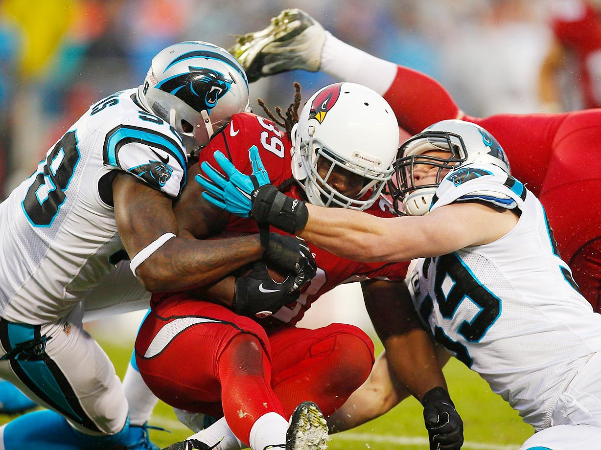 Arizona Cardinals running back Robert Hughes gets tackled by two Carolina Panthers during an NFC WIld Card playof game in Charlotte, N.C.