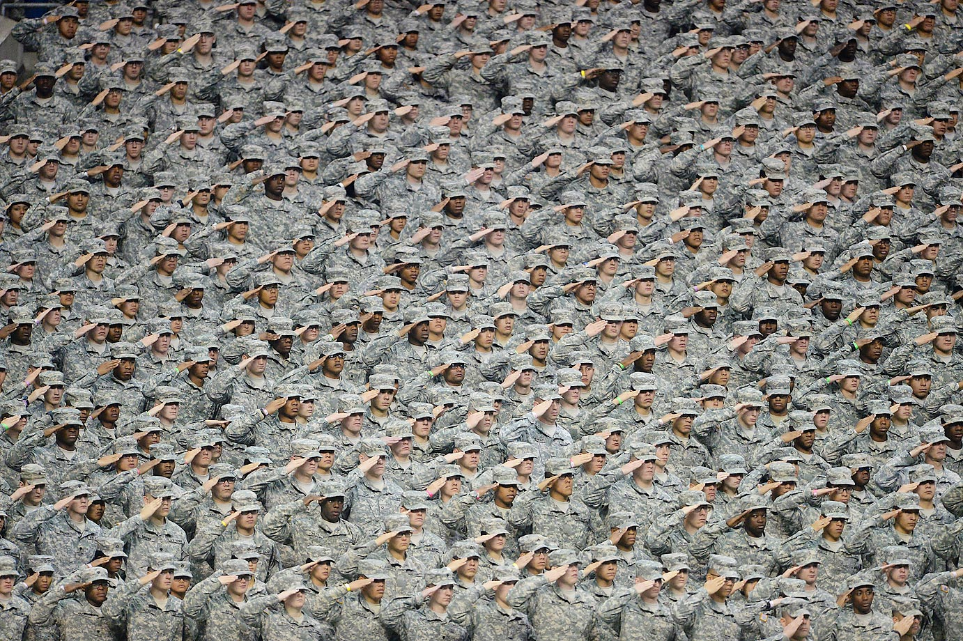 Members of the U.S. Army salute during the national anthem before the U.S. Army All-American Bowl in the Alamodome in San Antonio.