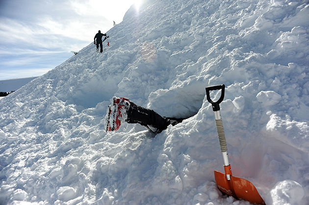 Breckenridge Ski Patroller Hunter Mortensen clears snow out of a pit where people will be buried to act as live victims for a dog rescuer training exercise as part of the Avalanche Deployment program at Vail Pass.