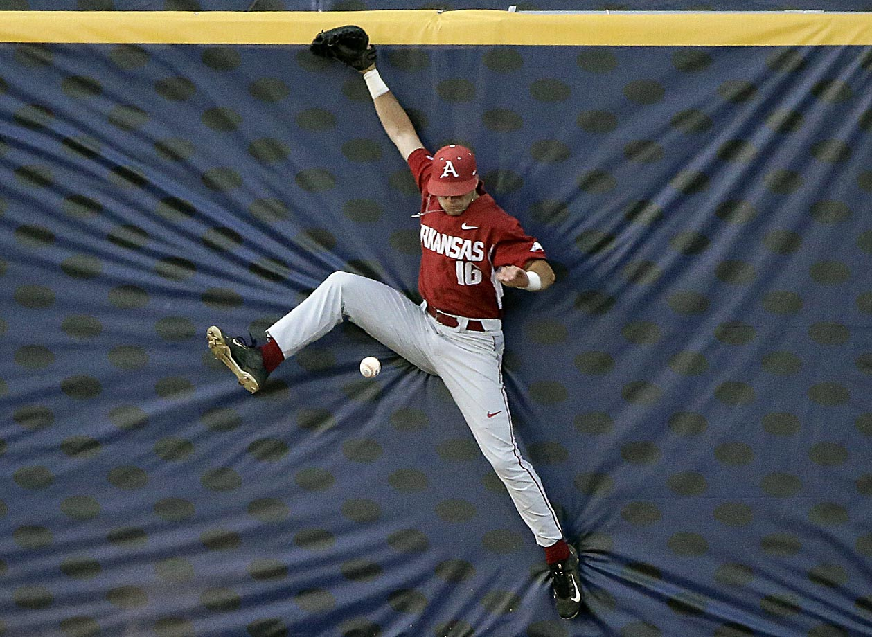Arkansas outfielder Andrew Benintendi jumps into the wall during a Southeastern Conference baseball tournament game against Florida.