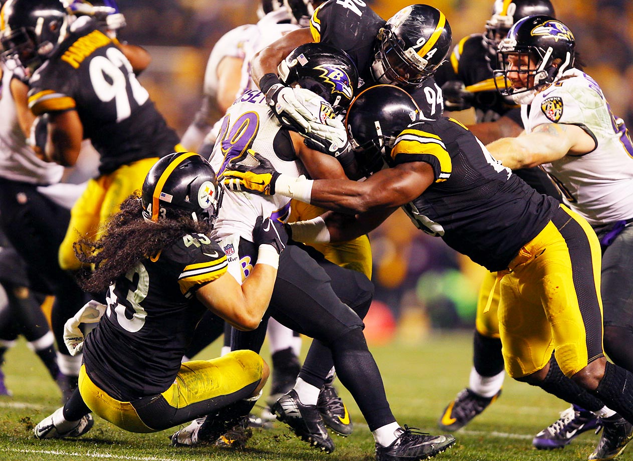 Baltimore Ravens running back Justin Forsett gets tackled by a horde of Pittsburgh Steelers defenders during an AFC Wild Card playoff game at Heinz Field in Pittsburgh