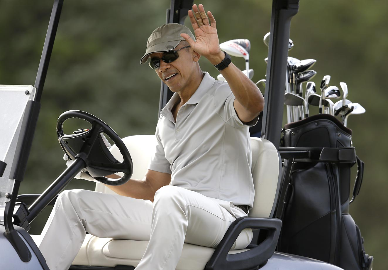 President Barack Obama waves to people from his cart while at Farm Neck Golf Club on Martha's Vineyard.