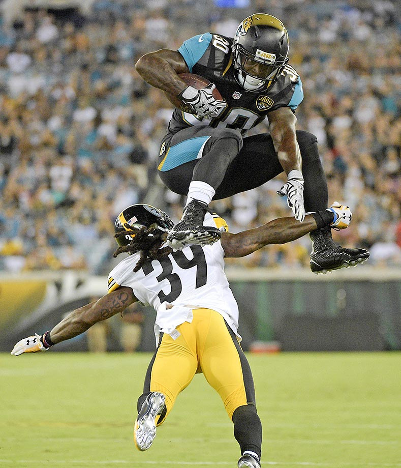 Jacksonville Jaguars running back Bernard Pierce leaps over Pittsburgh Steelers cornerback B.W. Webb.