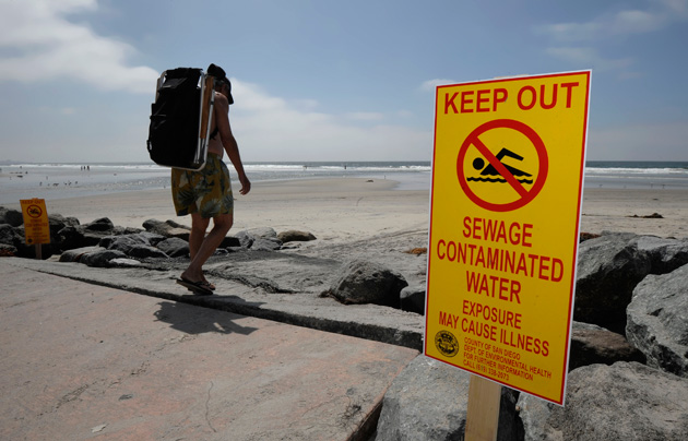 A beachgoer walks past a sign posted to warn people of contaminated water at Torrey Pines State Beach in San Diego. The Heal the Bay Beach Report Card provides a weekly analysis of coastline water quality on the West Coast, over 500 beaches are graded A to F based on bacteria analysis.
