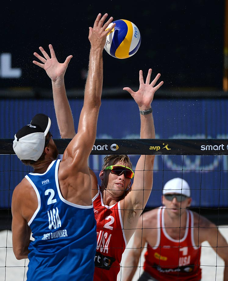 Theodore Brunner of the U.S. spikes the ball against Casey Patterson of the U.S. as Jake Gibb stands in the background in the semifinals.