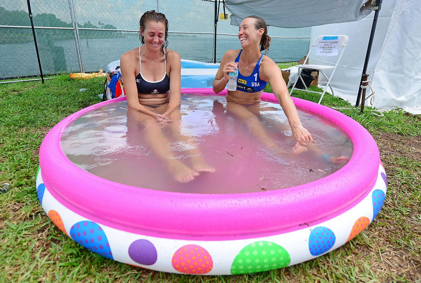 Jennifer Fopma and Lauren Fendrick sit in a pool to bring down their body temperatures in the 100 degree heat and 80 percent humidity during the FIVB Beach Volleyball World Tour in St. Petersburg, Fla.