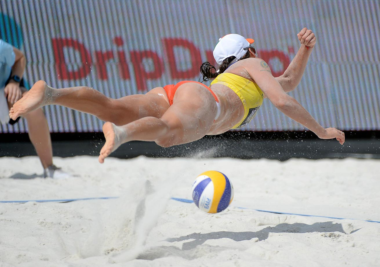 Taiana Lima of Brazil dives for the ball in the bronze medal game against Karla Borger and Britta Buth of Germany.