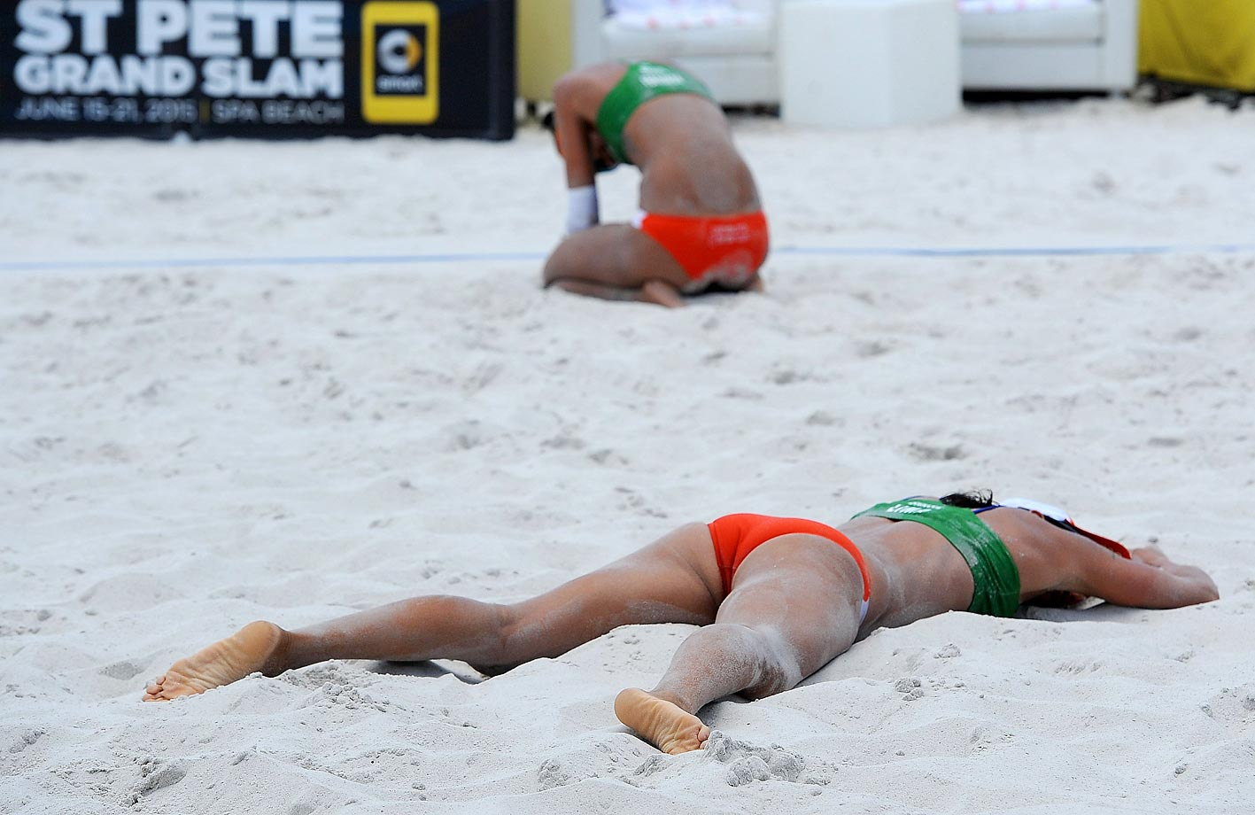 Fernanda Alves Berti and Taiana Lima of Brazil collapse at the final point during their bronze medal game against Karla Borger and Britta Buthe of Germany in the FIVB Beach Volleyball World Tour.