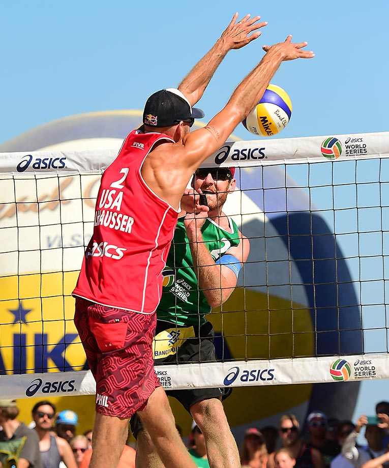 Alison Cerutti of Brazil tries to sneak one by Phil Dalhausser in the final.