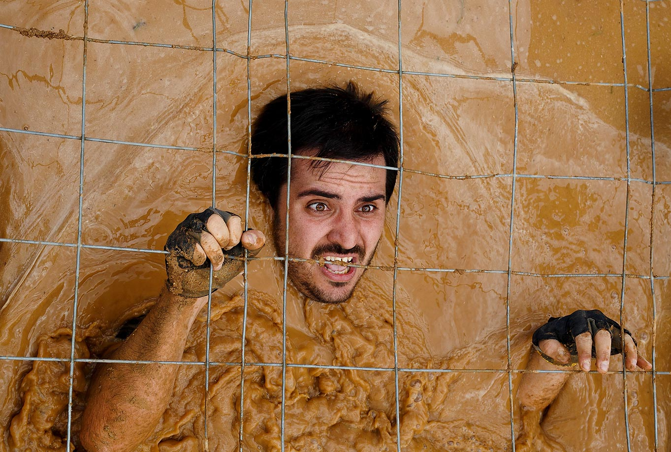 A competitor passes under a fence through the water during the first Belik obstacle course race, held near Guadalajara, Spain.