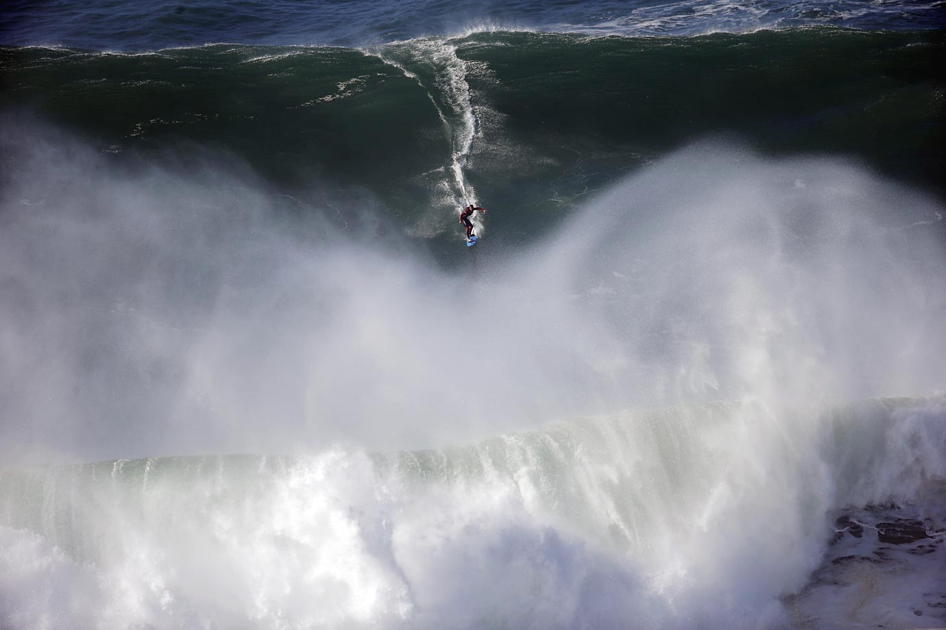 A surfer rides a wave during a tow-in surfing session at the Praia do Norte beach in Nazare, Portugal.