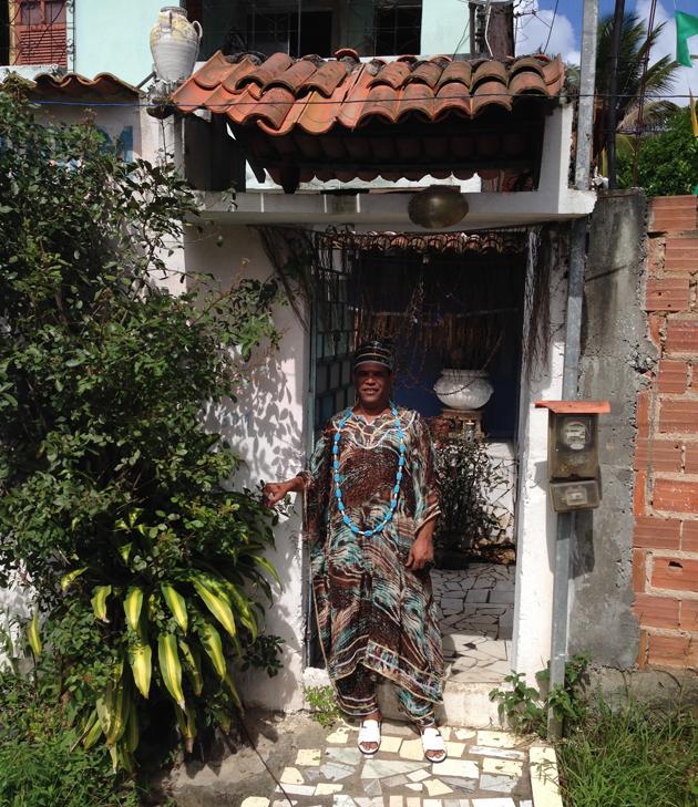 Gilson Ferreira dos Santos, a Pai de Santo in Candomble, the mystical Brazilian religion, sits outside his home in Salvador.