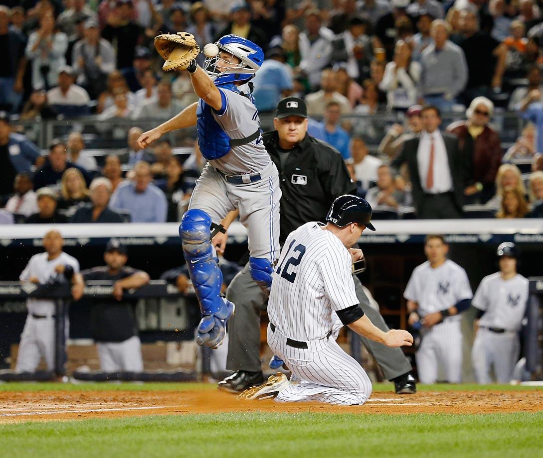 Chase Headley slides home safely past Josh Thole.  The Yankees won 3-2 over the Jays.
