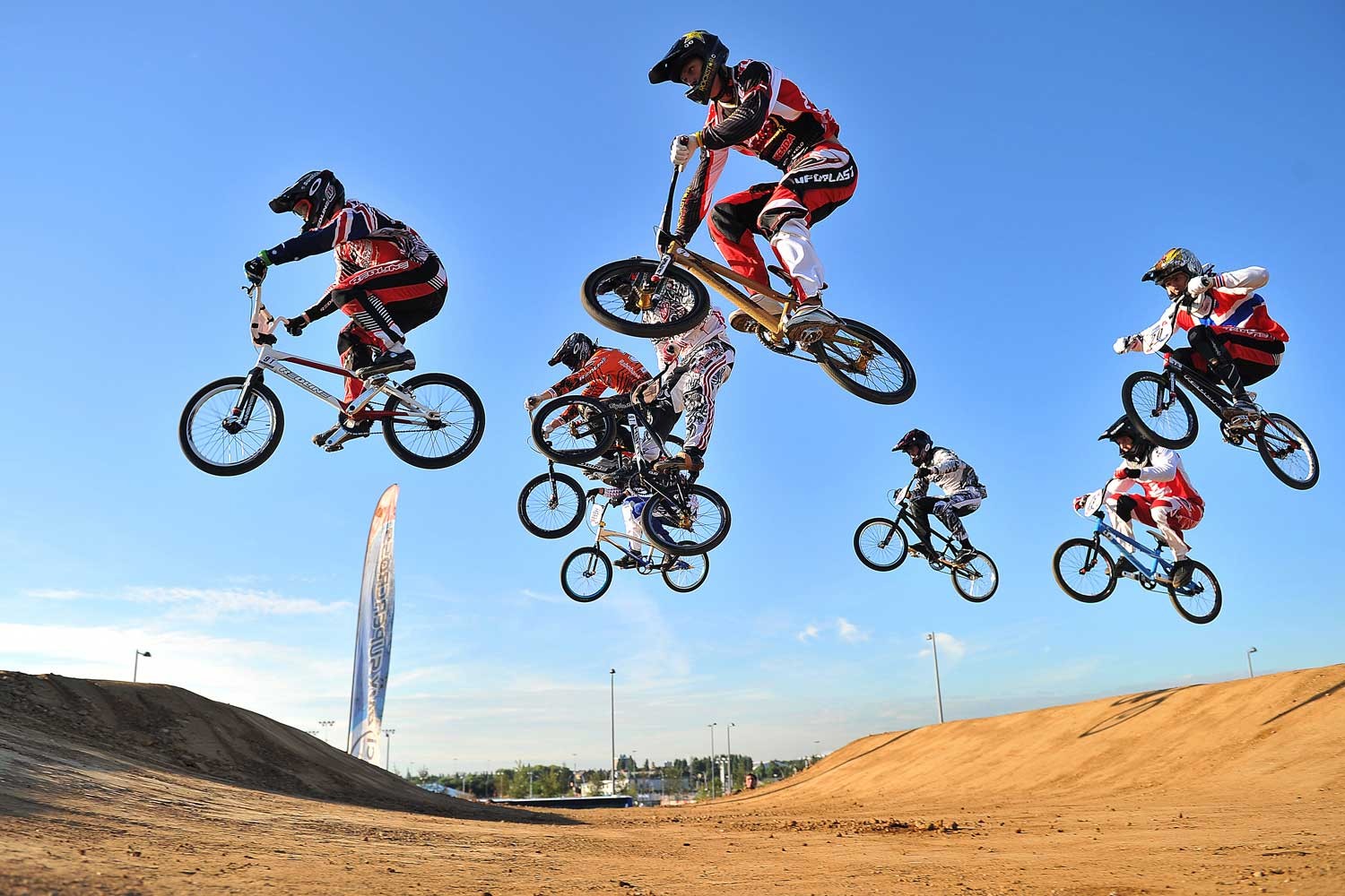 Riders fly over a jump while competing in the UCI BMX Supercross World Cup.