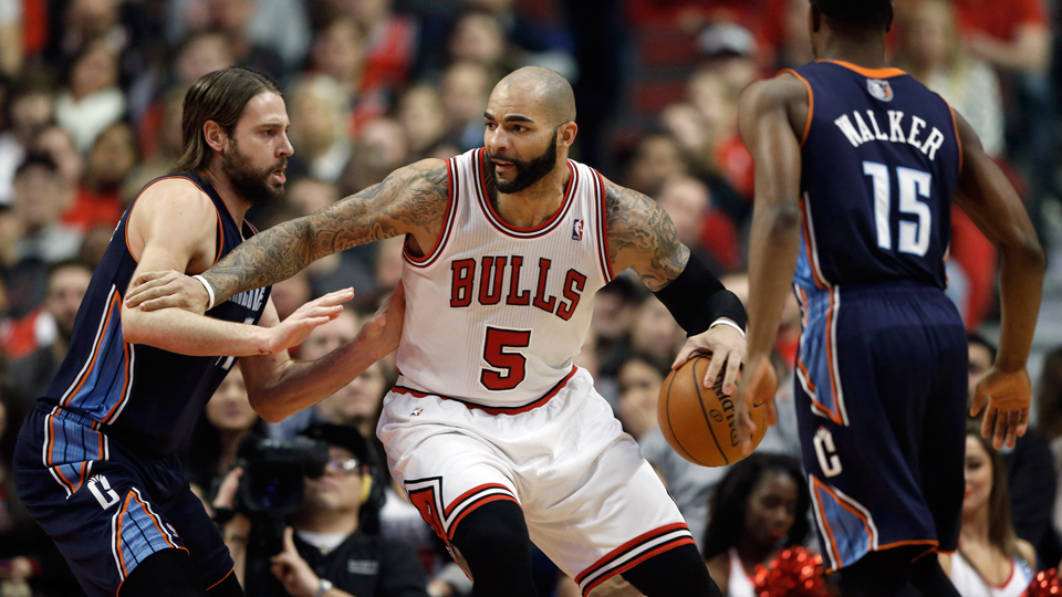 Chicago Bulls forward Carlos Boozer, center, looks for a way to the basket against Charlotte Bobcats forward Josh McRoberts, left, while Charlotte Bobcats guard Kemba Walker looks on.
