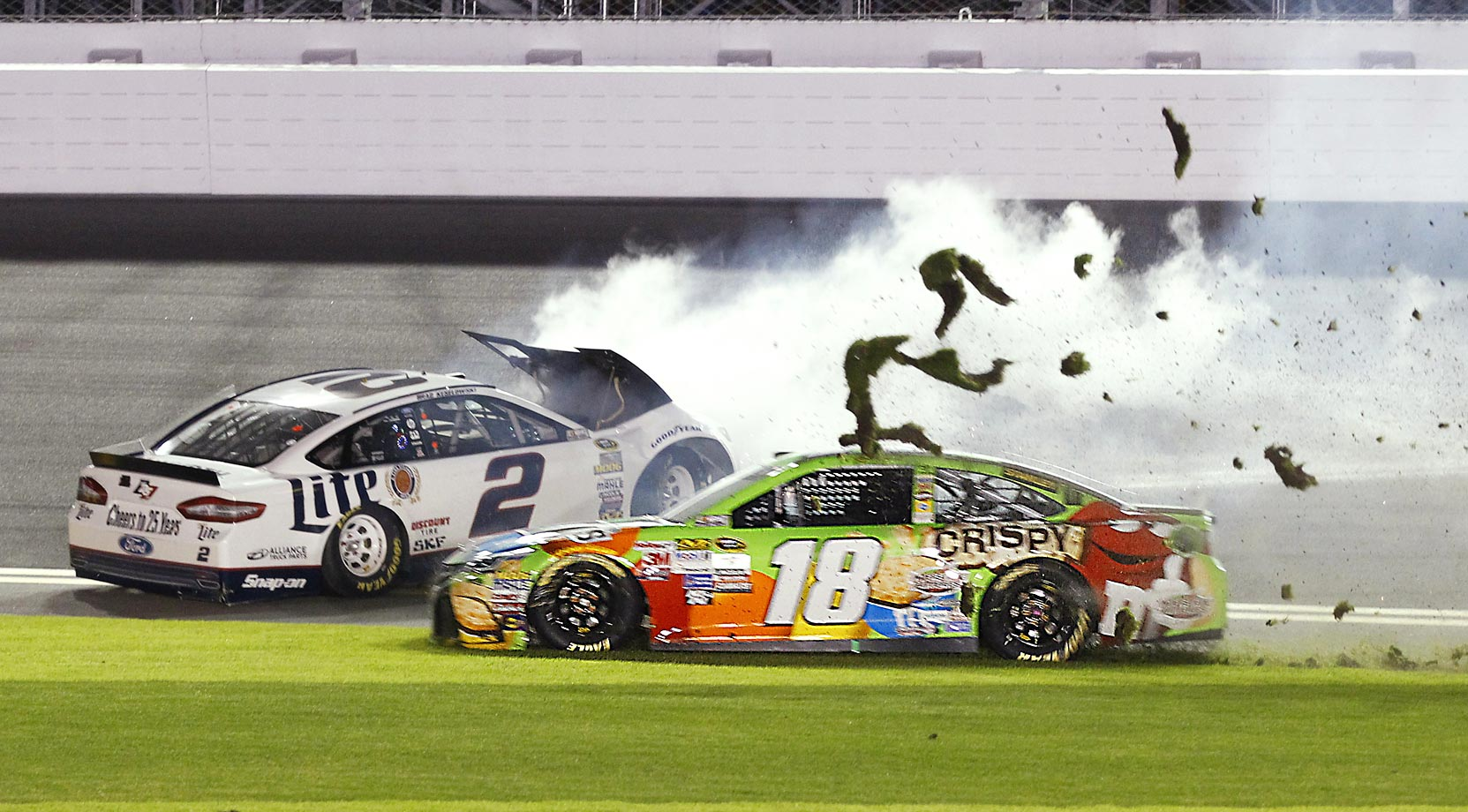 Brad Keselowski (2) slides backward after hitting the wall in the front stretch and Kyle Busch (18) drives through the infield grass to avoid him during the NASCAR Sprint Unlimited race at Daytona International Speedway.