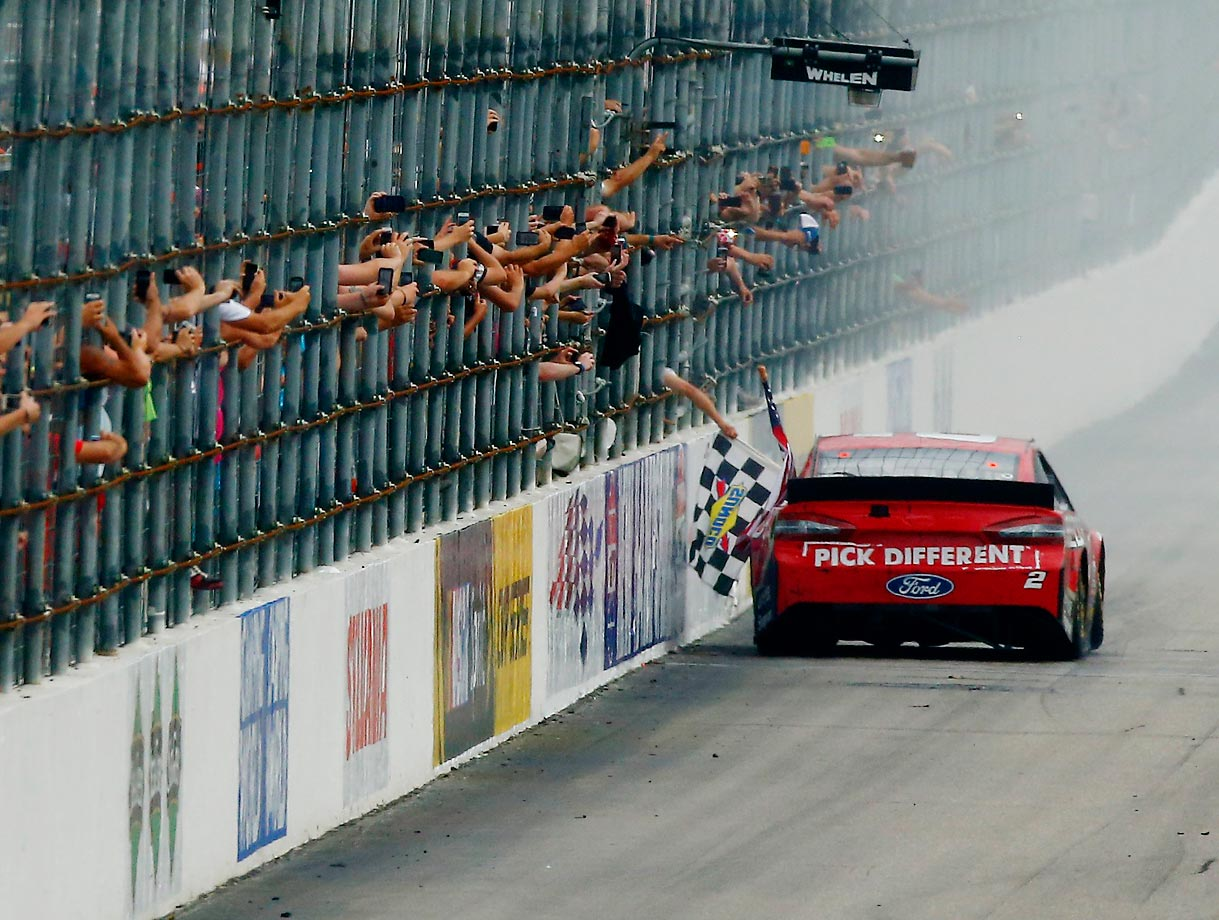 Fans take pictures as Brad Keselowski, driver of the #2 Redds Ford, celebrates after winning the NASCAR Sprint Cup Series Camping World RV Sales 301 at New Hampshire Motor Speedway on July 13, 2014 in Loudon, New Hampshire.