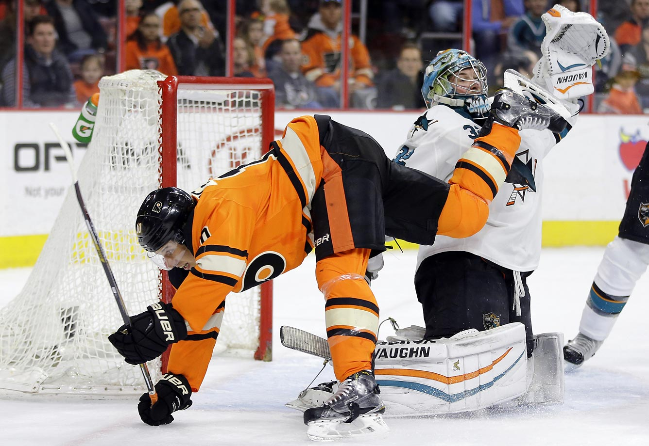 Brayden Schenn of the Flyers collides with Alex Stalock of the Sharks.
