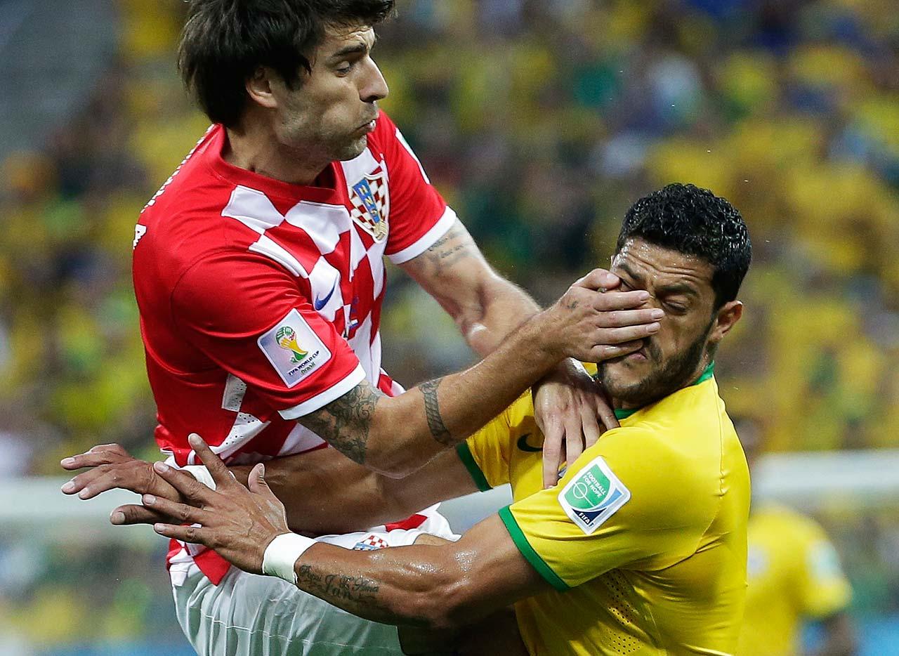 Croatia's Vedran Corluka, left, clashes with Brazil's Hulk.