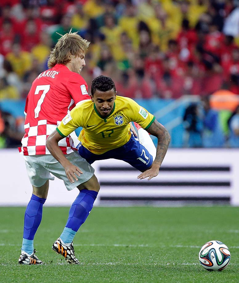 Brazil's Luiz Gustavo, right, is challenged by Croatia's Ivan Rakitic during Brazil's 3-1 victory over Croatia in the opening game of the 2014 tournament, in the Itaquerao Stadium in Sao Paulo, Brazil.