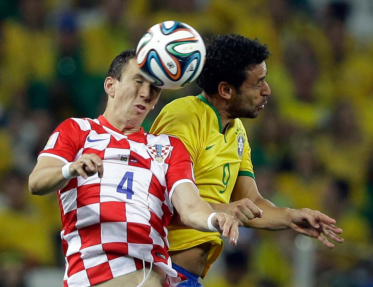 Croatia's Ivan Perisic, left, wins a header from Brazil's Fred.