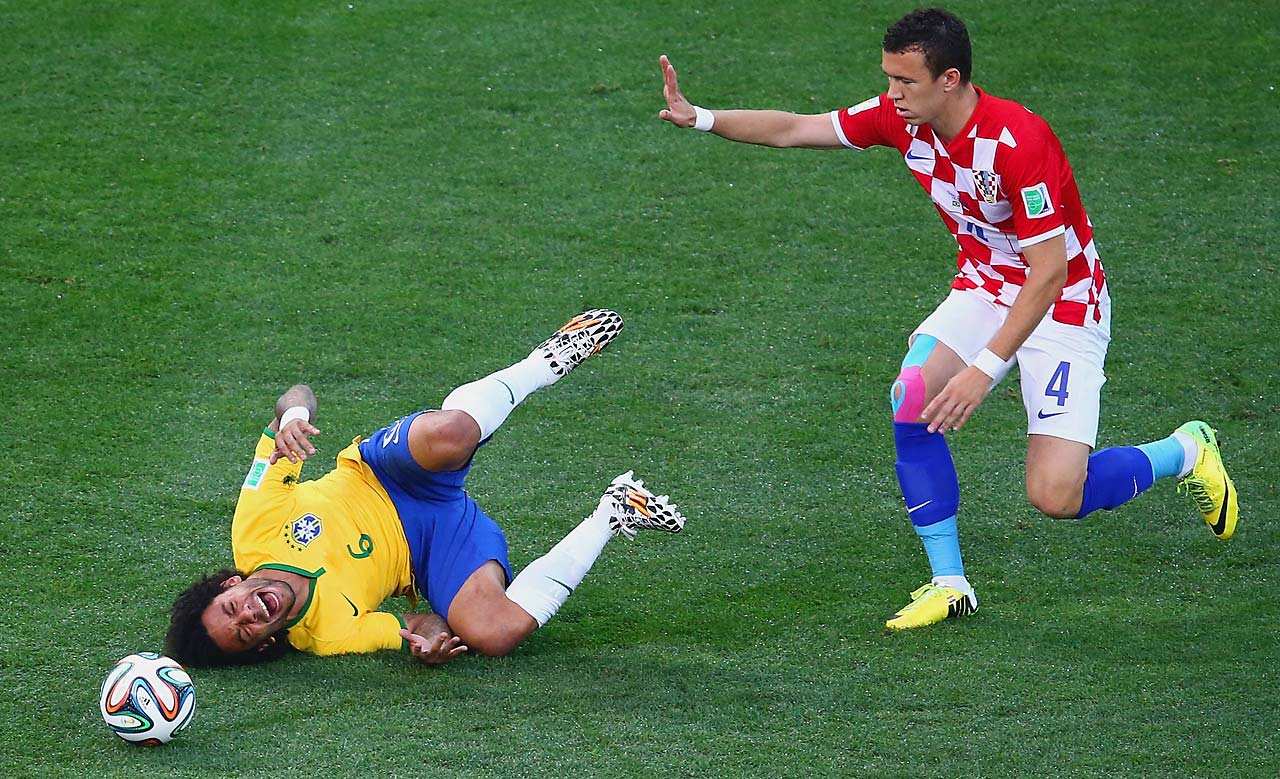 Marcelo of Brazil falls after a challenge by Ivan Perisic of Croatia.