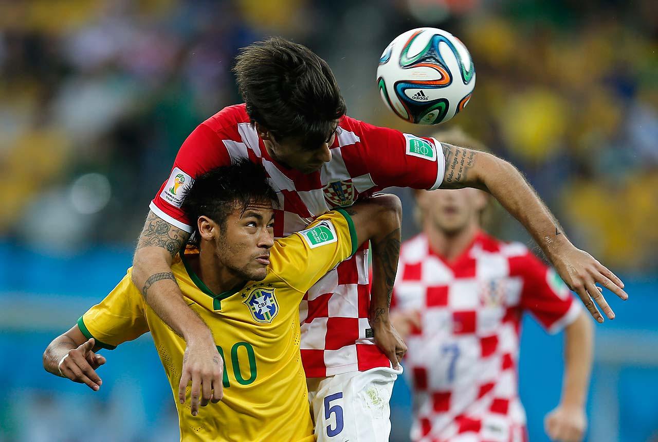 Neymar and Vedran Corluka challenge for the ball.