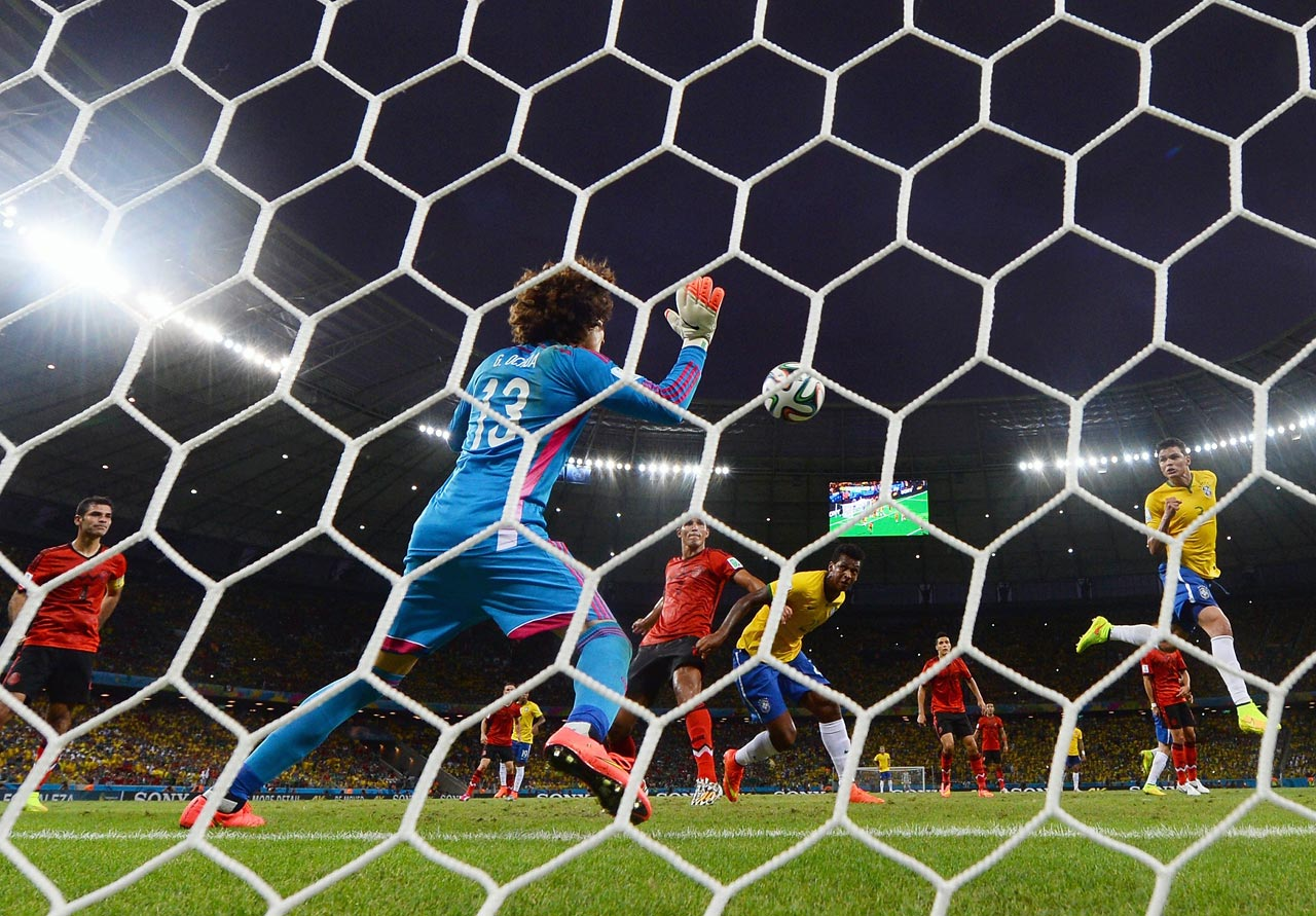 Brazil captain Thiago Silva's header is stuffed by Mexico goalkeeper Guillermo Ochoa, who made six saves in a thrilling 0-0 draw in Group A play.