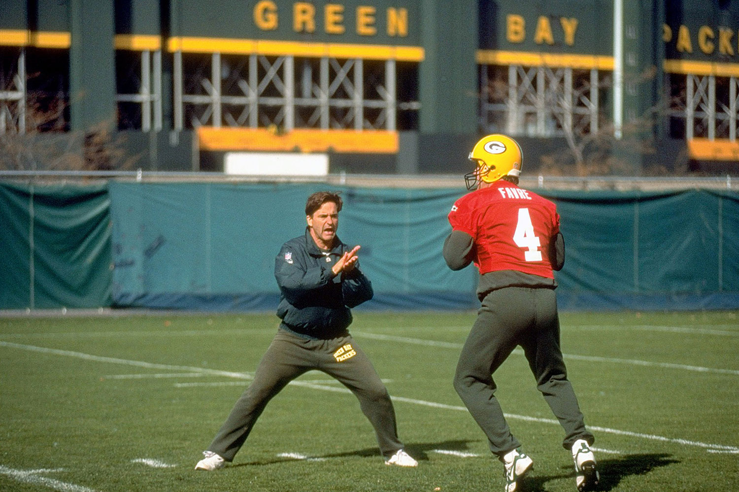 Brett Favre working with quarterbacks coach Steve Mariucci during practice outside of Lambeau Field.