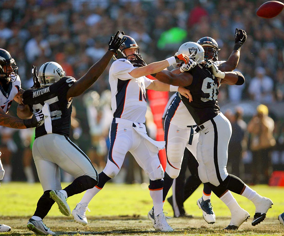 Denver Broncos quarterback Peyton Manning gets a pass off against Oakland Raiders defenders. Manning threw for 340 yards with five touchdowns and two interceptions in the Broncos' win.