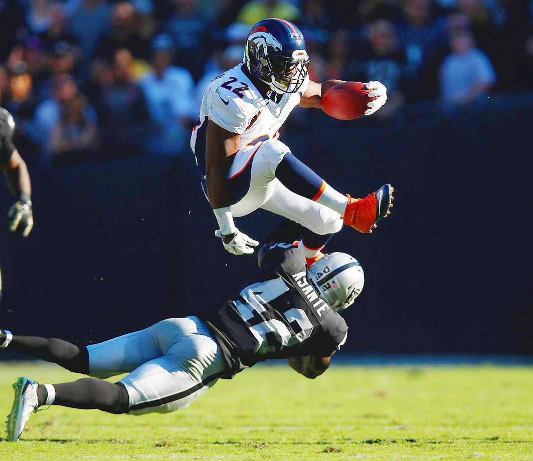 Denver Broncos running back C.J. Anderson leaps over Oakland Raiders defensive back Larry Adande. The Broncos defeated the Raiders 41-17.
