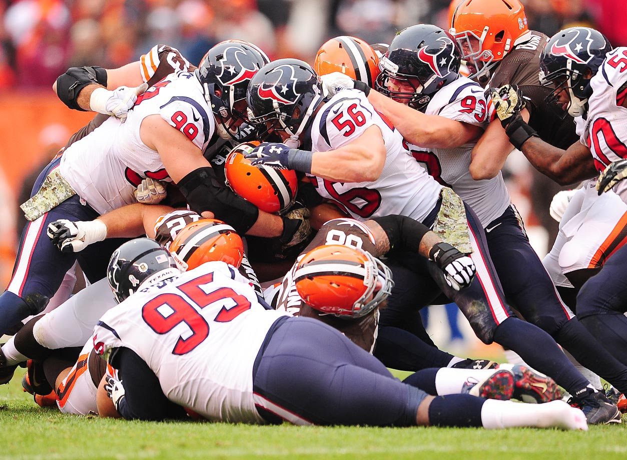 Houston Texans defensive end J.J. Watt and linebacker Brian Cushing tackle Cleveland Browns quarterback Brian Hoyer. The Texans won the road game 23-7.