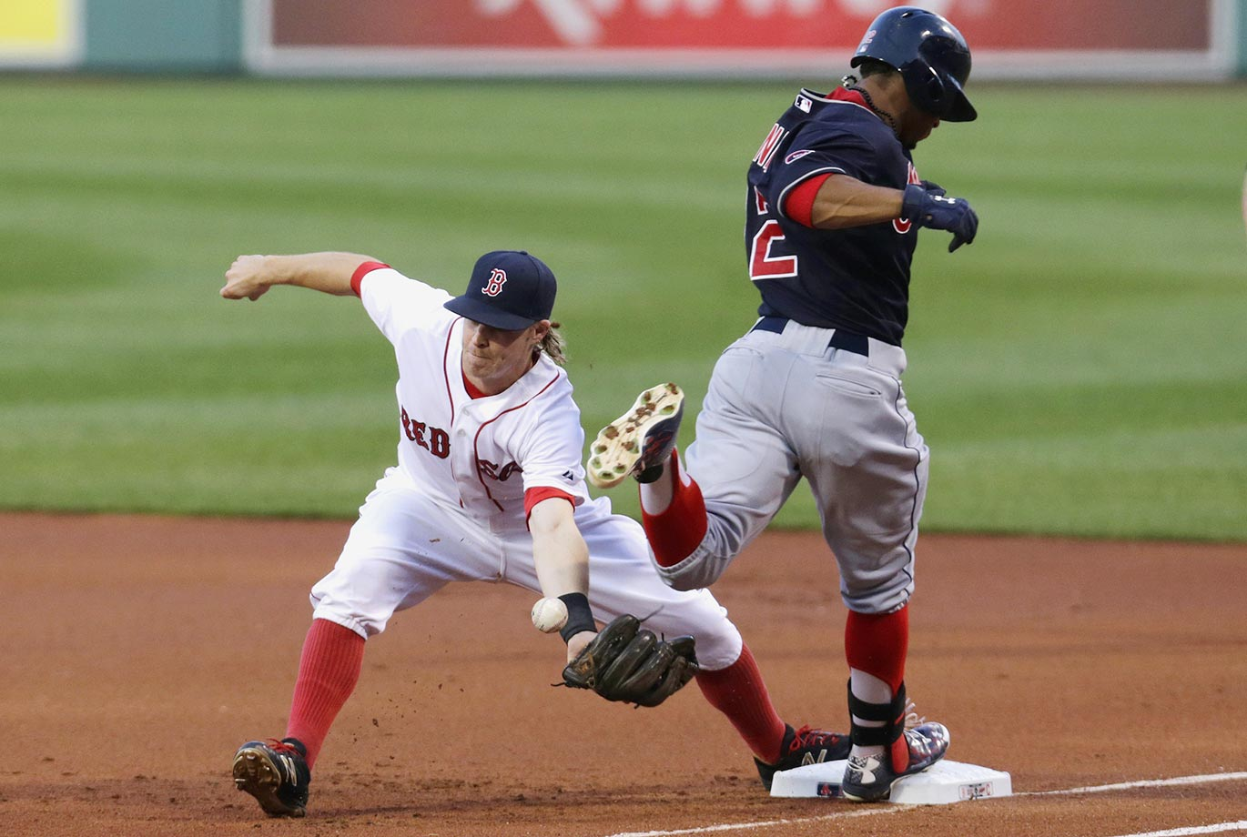 Boston Red Sox second baseman Brock Holt drops the ball for an error while covering first base on a grounder by Cleveland Indians Francisco Lindor.