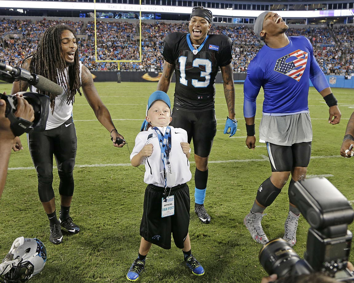 Carolina Panthers players Cam Newton, Kelvin Benjamin and Tre Boston laugh as Braylon Beam dances during the annual Fan Fest at training camp in Charlotte.